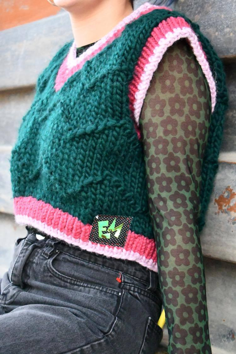 A closeup shot of Walsh's handmade green sweater with pink trim
