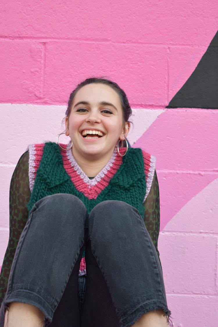 Emma Walsh models one of her sweaters while seated against a painted pink wall in Texas