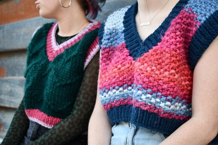 two models sit next to eachother wearing colorful handmade sweaters
