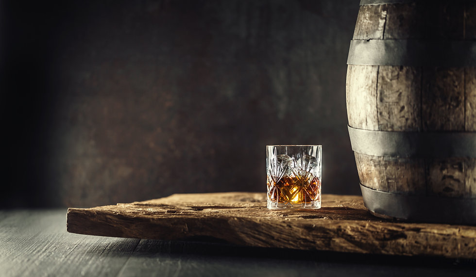 Glass of whisky cognac or bourbon in ornamental glass next to a vinatge wooden barrel on a