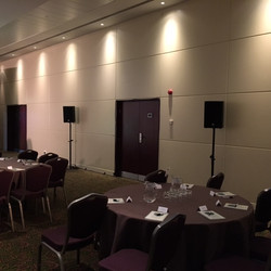 HK speakers on floor stands in a conference