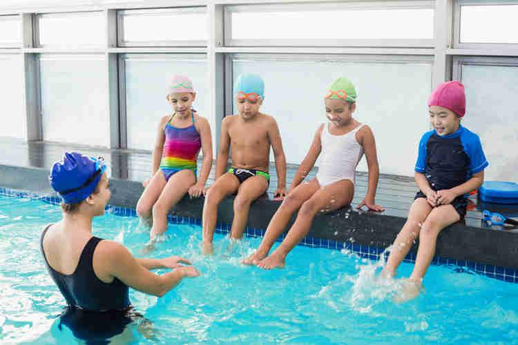 smiling children splashing swim coach while sitting alongside pool