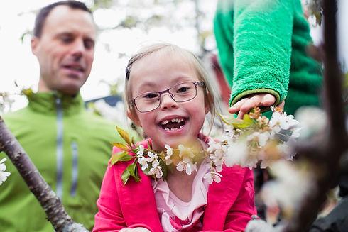 ein lachendes Mädchen mit einer Beeinträchtigung, Blumen um den Hals und ihre Eltern im Hintergrund