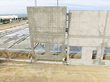 Construction workers putting up cement wall panel