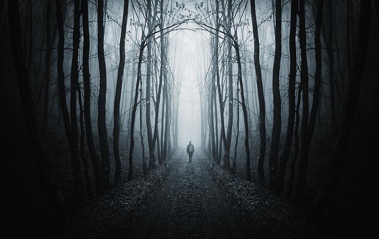 man walking on a path in a strange dark