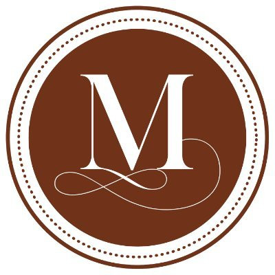 Text: the letter M in a circle and a brown background.