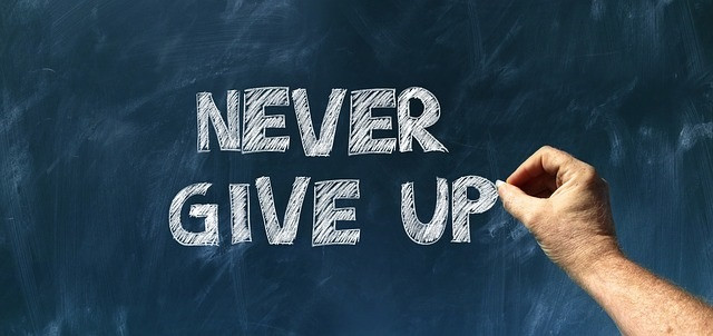 """A chalkboard with the words """"Never give up."""""""