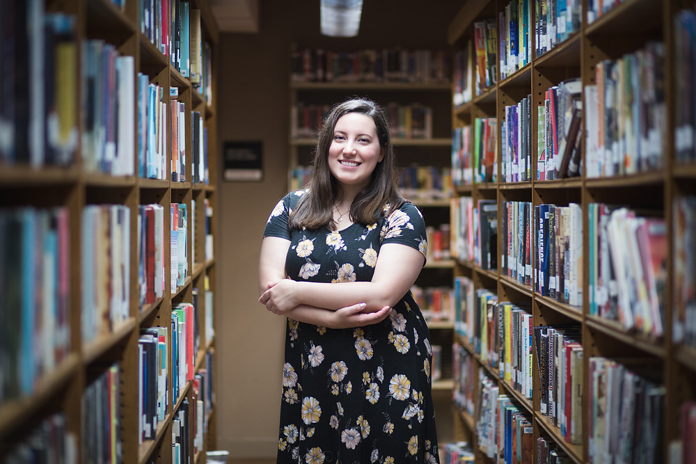 Ashley Dufault, writer, standing between two aisles of books at Ames Free Library in North Easton, Massachusetts