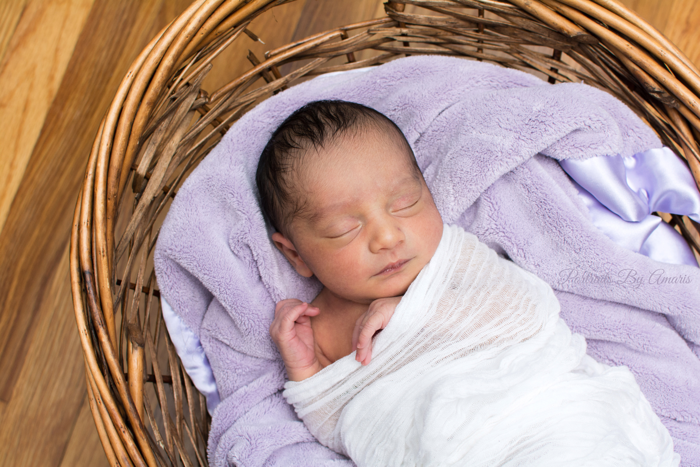 Newborn girl with purple blanket
