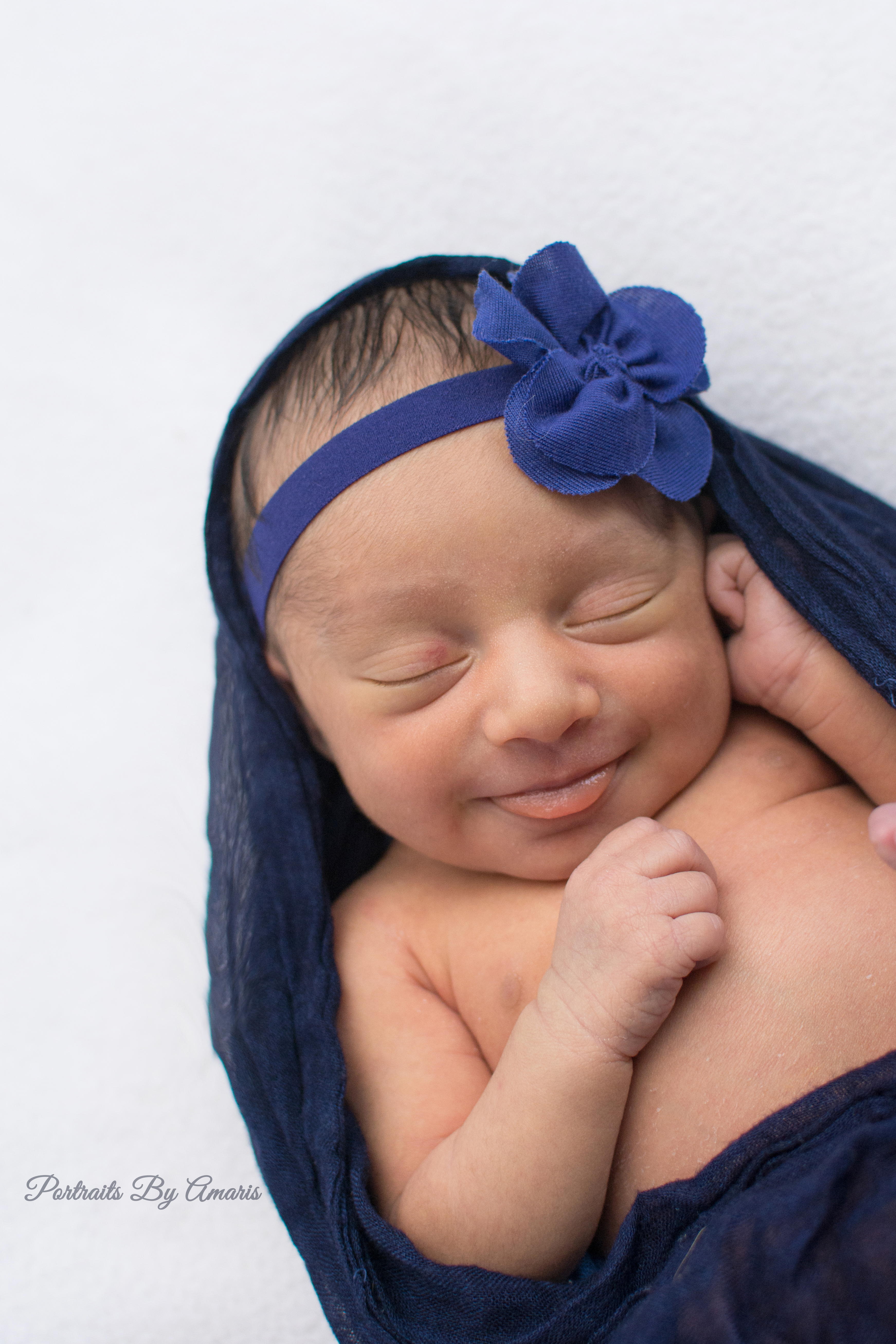 Newborn girl smiling in blue
