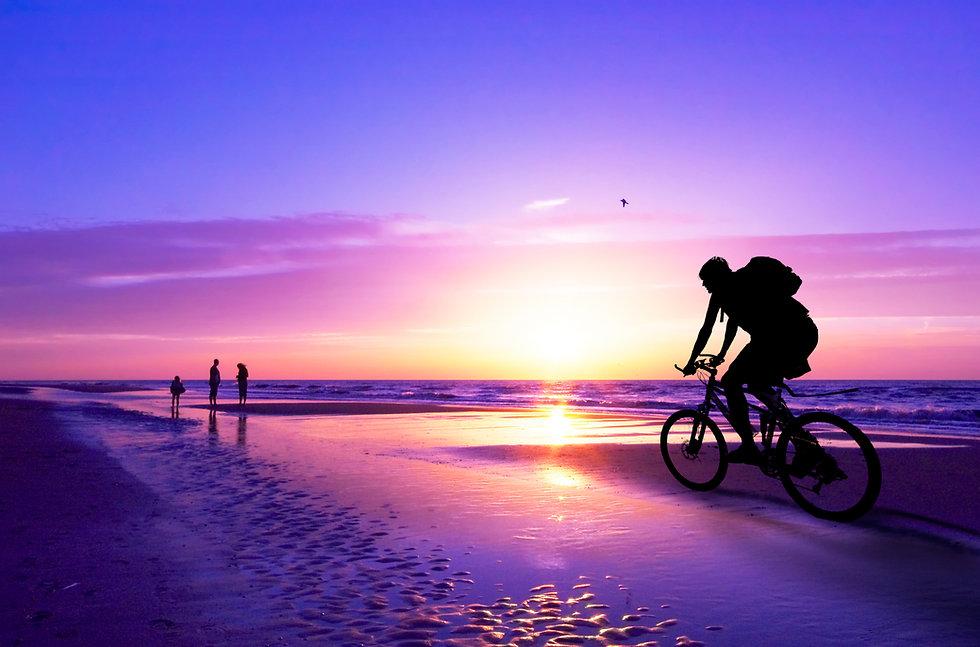 silhouette of a mountain biker on beach