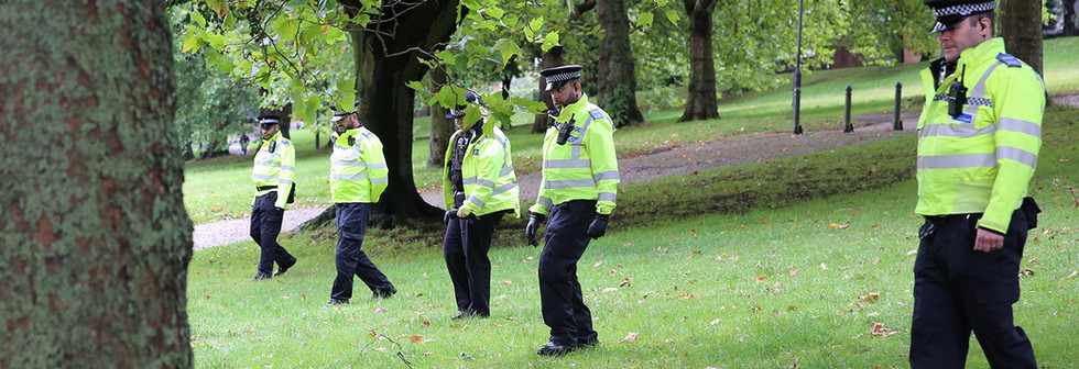 Officers sweeping for weapons in wooded