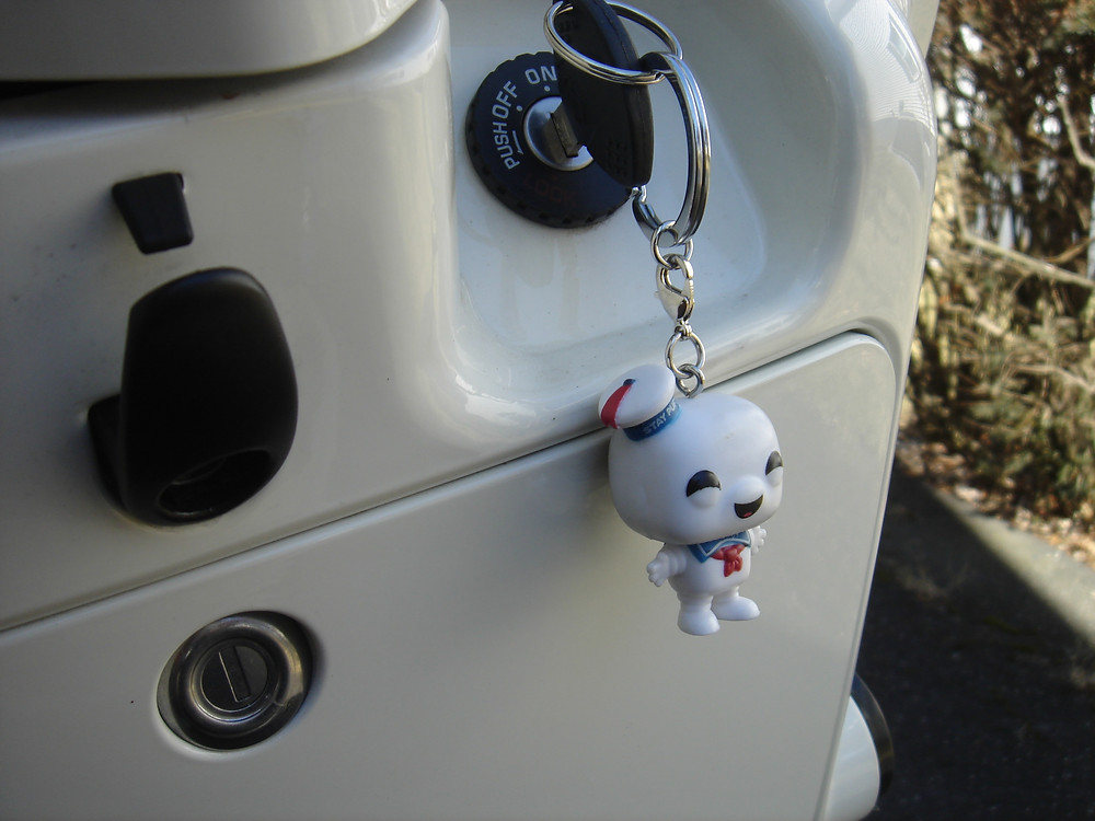 Ghostbusters Stay-Puft Marshmallow Man keychain hanging on a Kymco scooter.