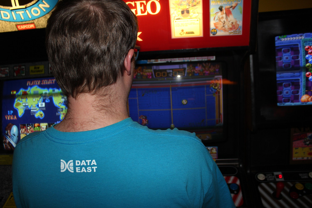Man playing Data East's Windjammers on a Neo-Geo MVS.