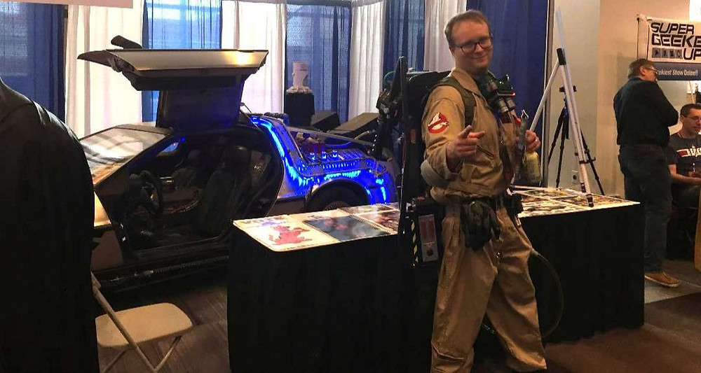 A Ghostbuster stands in front of the Back to the Future DeLorean.