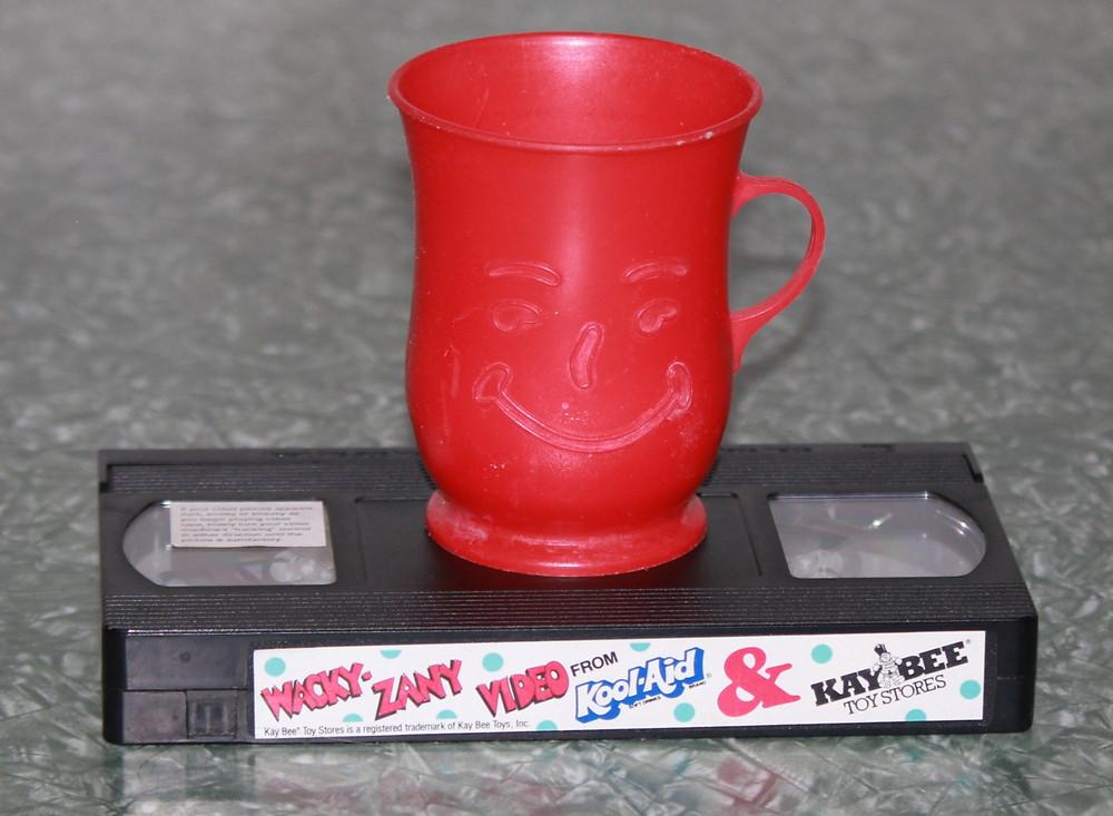 vintage '90s Kool-Aid cup and Kay-Bee Toys Wacky Zany VHS tape