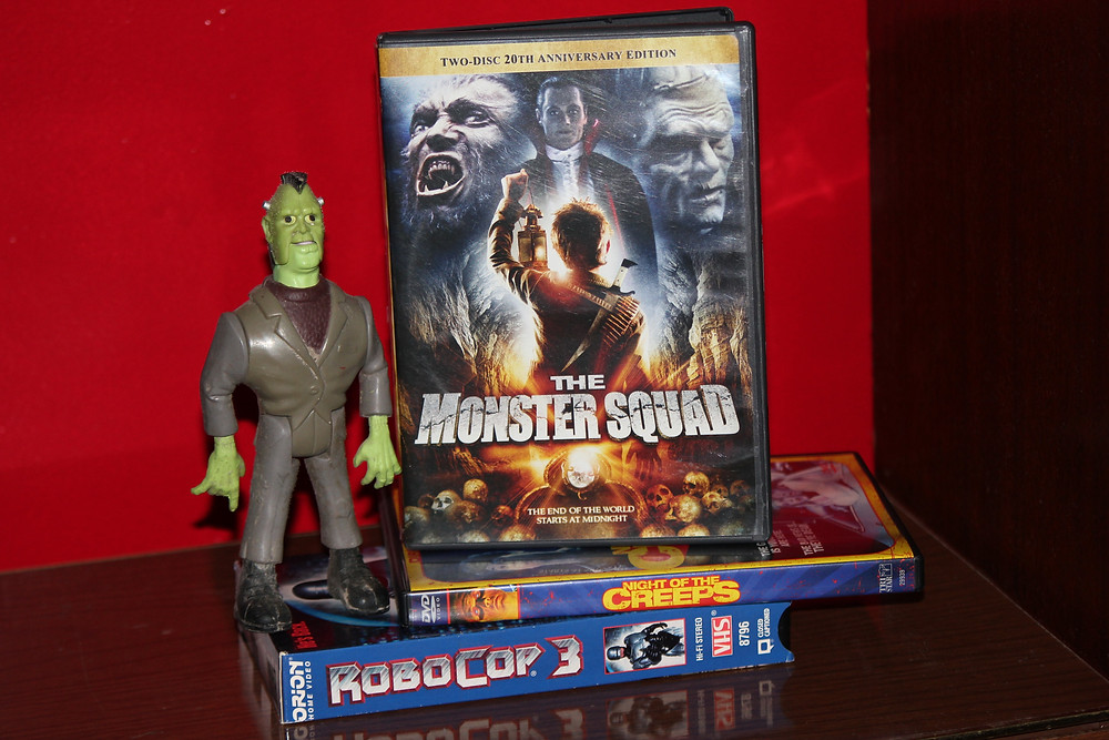The Real Ghostbusters Frankenstein Monster with The Monster Squad DVD, Night of the Creeps DVD and a RoboCop 3 VHS tape.