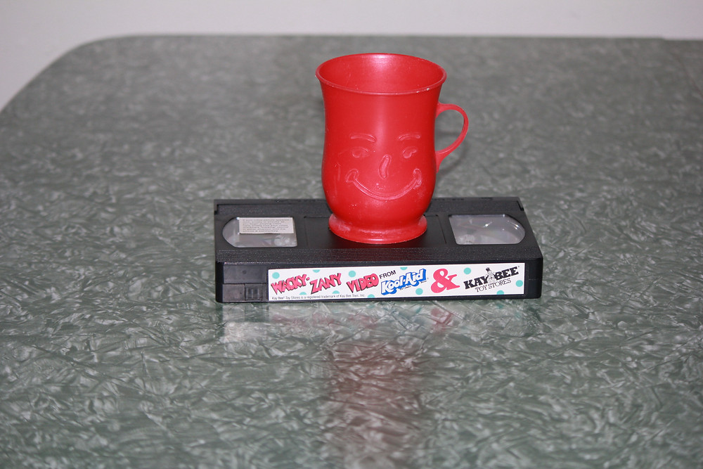Kool-Aid & Kay Bee Toystores Wacky-Zany Video cassette and red Kool-Aid cup.