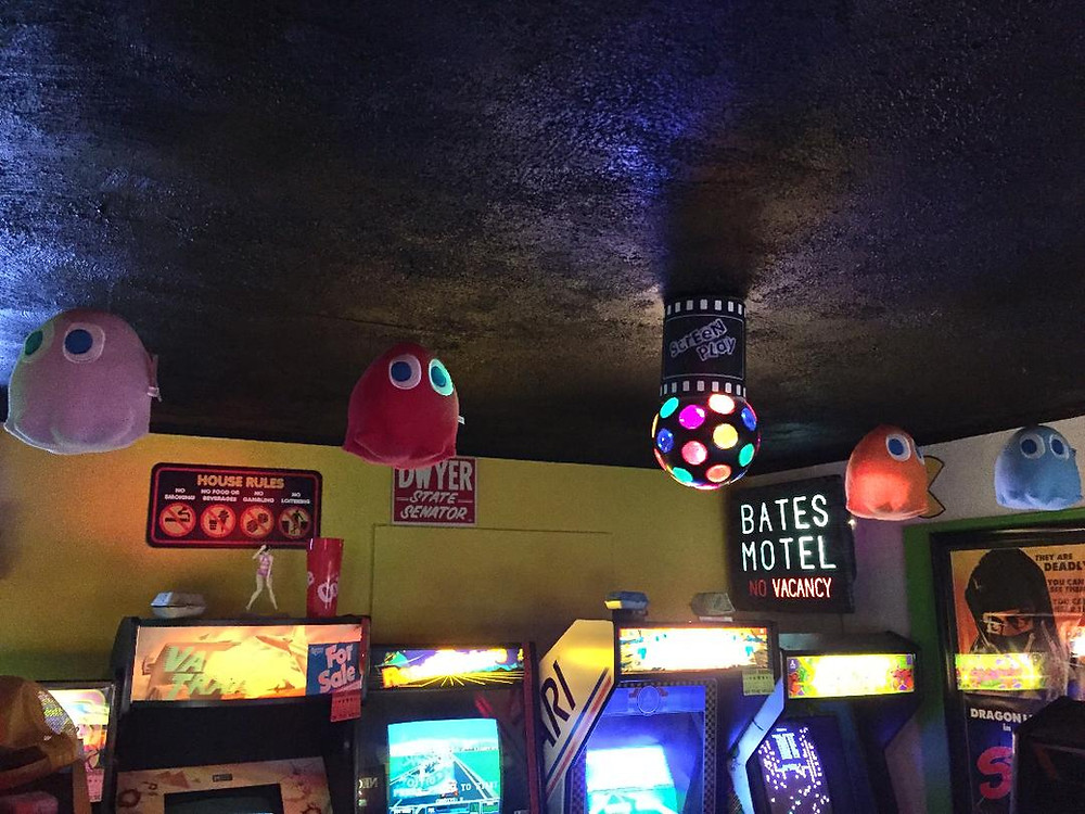 Pac-Man ghosts hanging in a  home arcade.