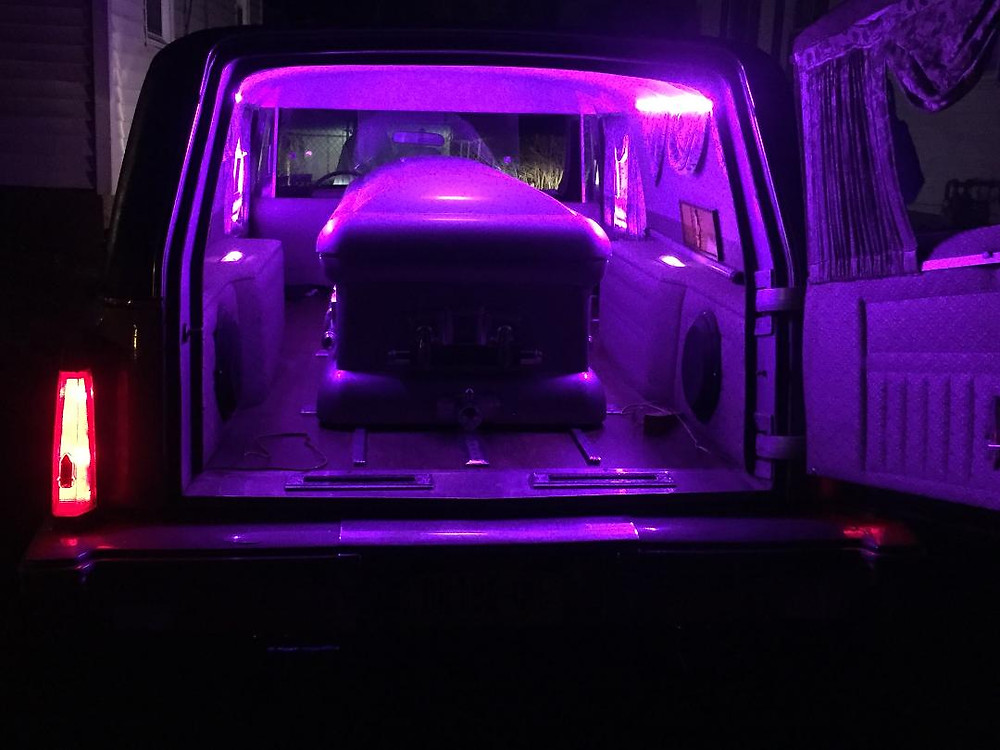 Casket in 1987 Cadillac Fleetwood hearse with custom lighting.