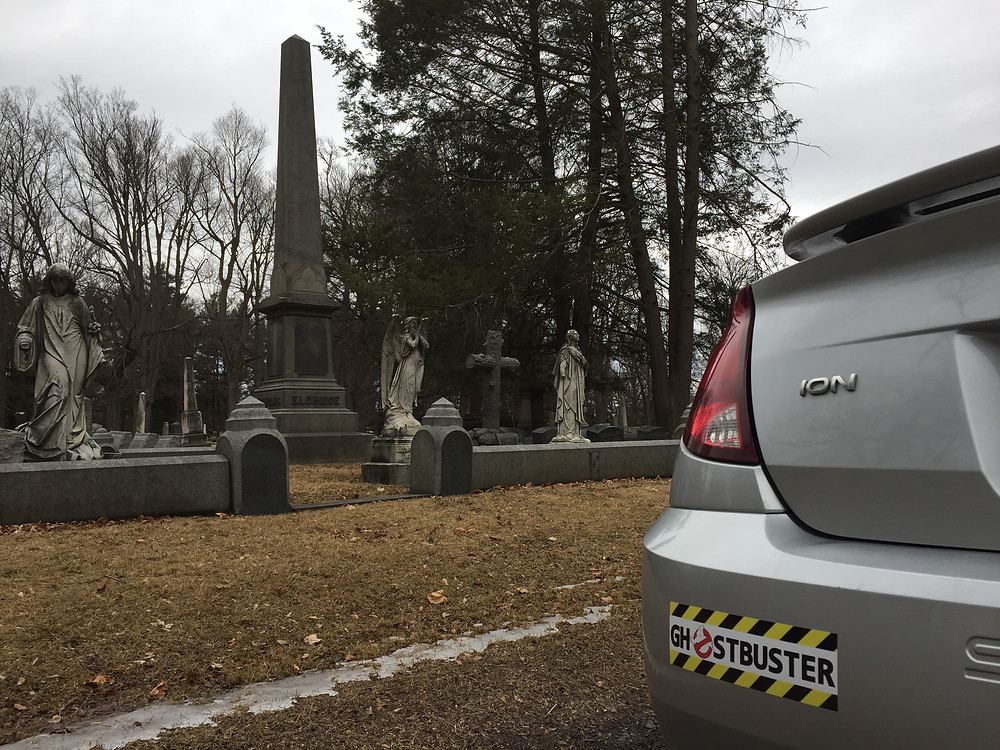 Ghostbuster bumper sticker on a Saturn Ion in a cemetery.