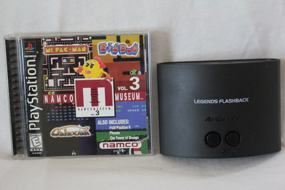 AtGames Legends Flashback console next to PlayStation Namco Museum Vol. 3