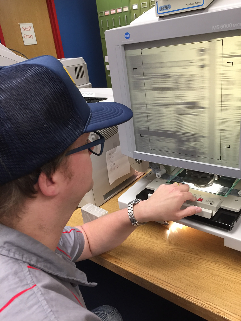 Using microfilm for library research.