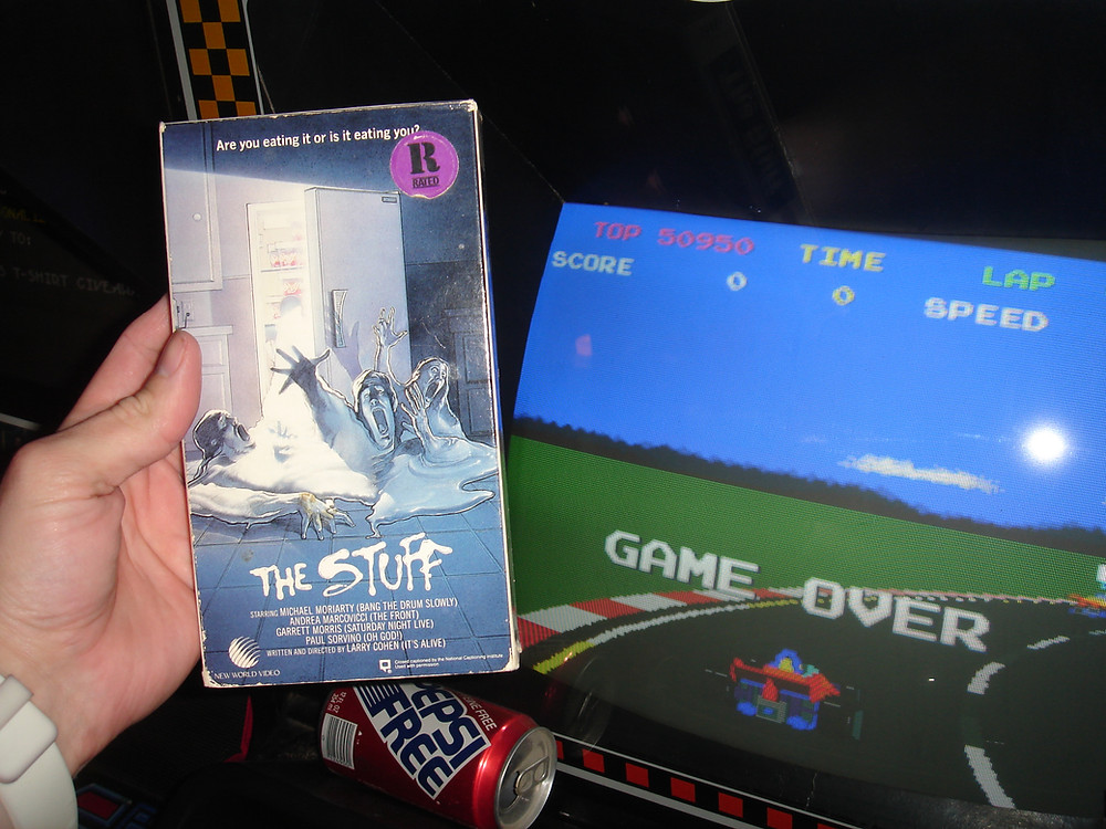 The Stuff VHS movie box in front of Pole Position arcade machine.