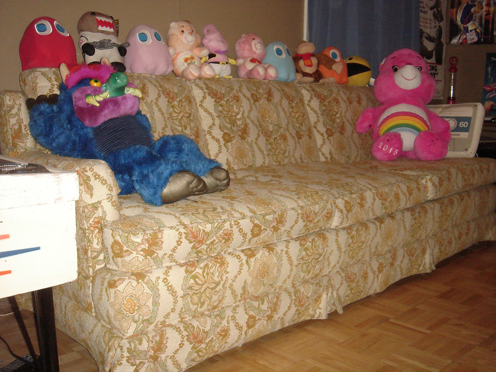 Cheer Bear Care Bear, My Pet Monster, Pac-Man, Donkey Kong, DragonBall Z plush toys on vintage couch.