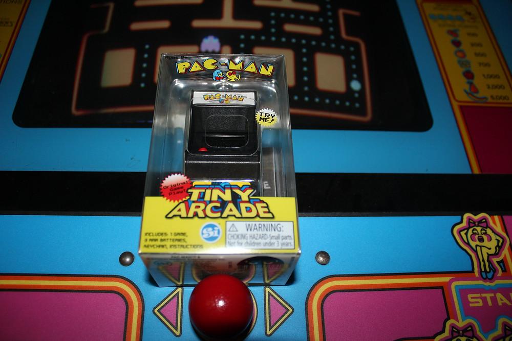 Super Impulse Tiny Arcade PAC-MAN key chain on Ms. PAC-MAN arcade cabinet.