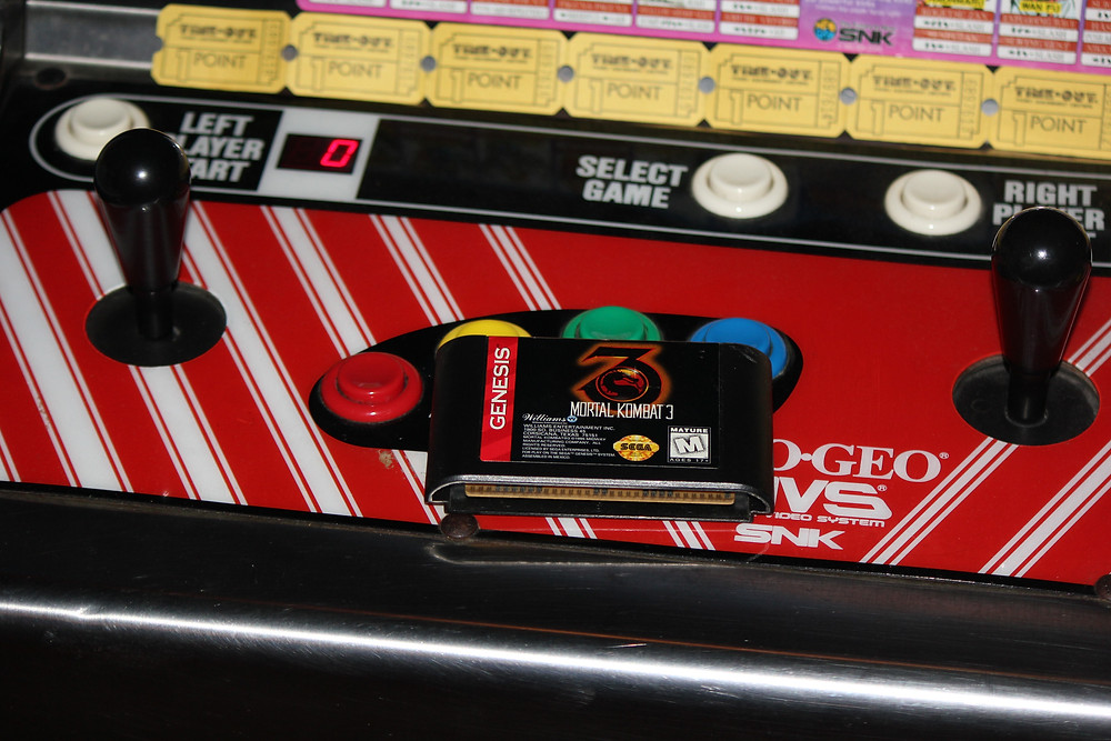 Sega Genesis Mortal Kombat 3 cartridge on a Neo-Geo arcade cabinet.
