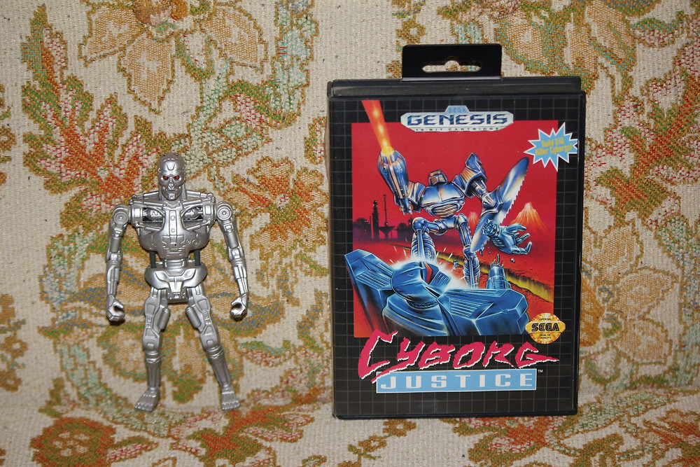 Cyborg Justice Sega Genesis cartridge with Kenner Terminator 2: Judgement Day action figure.