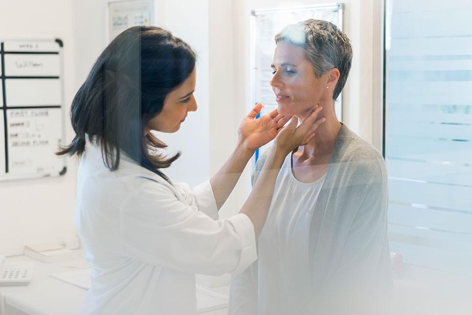 Médica analisando tireoide de paciente