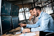Two men traders sitting at desk at offic