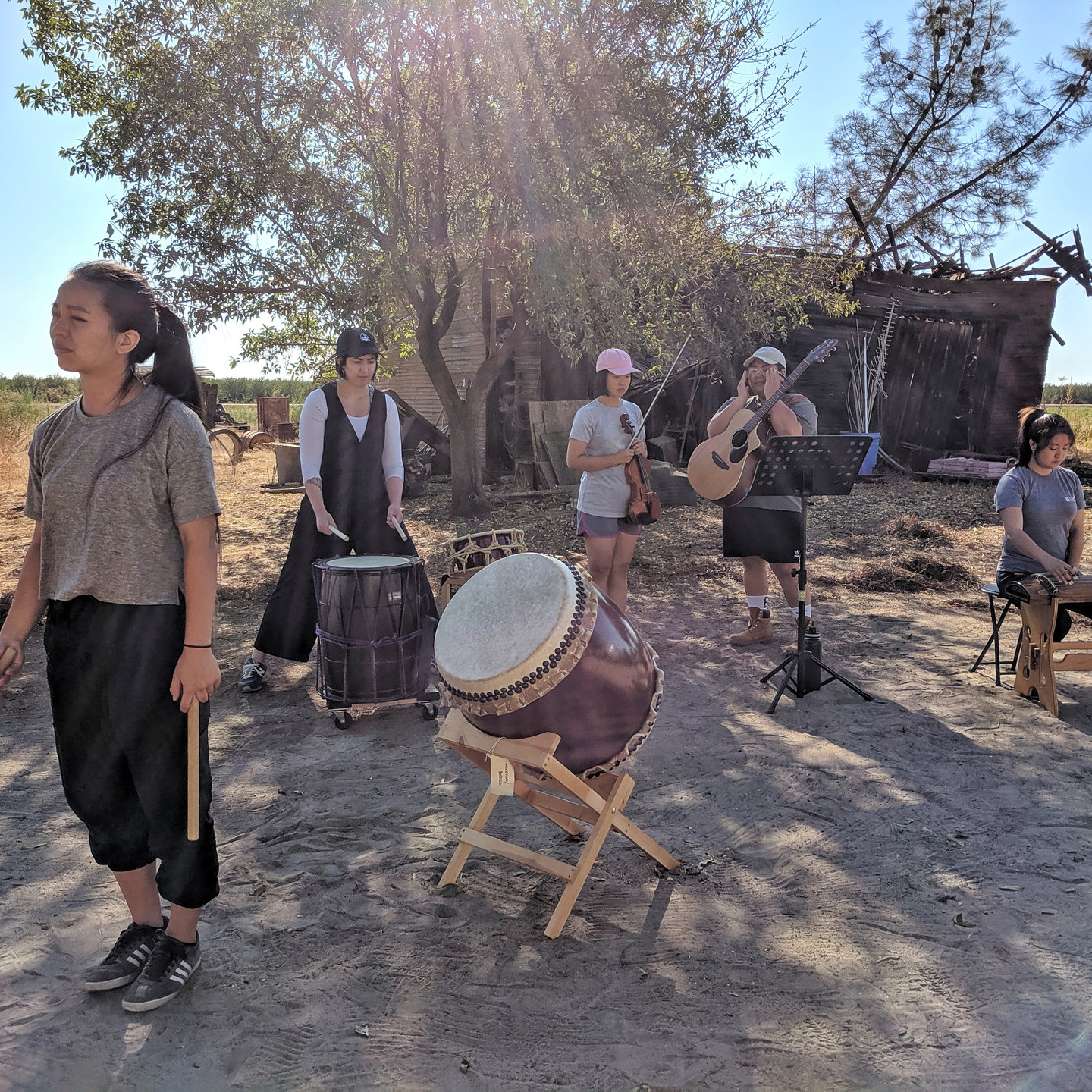 """Picture of performers doing a run-through of their piece, """"Ways of Being"""". Set up includes two taiko players in position; a violinist and guitarist reading music from a stand; and a person seated playing a koto. Behind them is worn down shack and an expanse of field."""