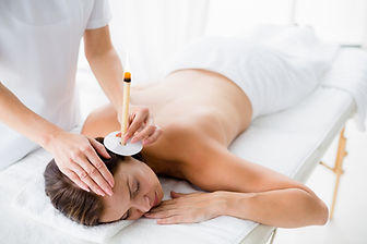 naked-woman-receiving-ear-candle-treatme