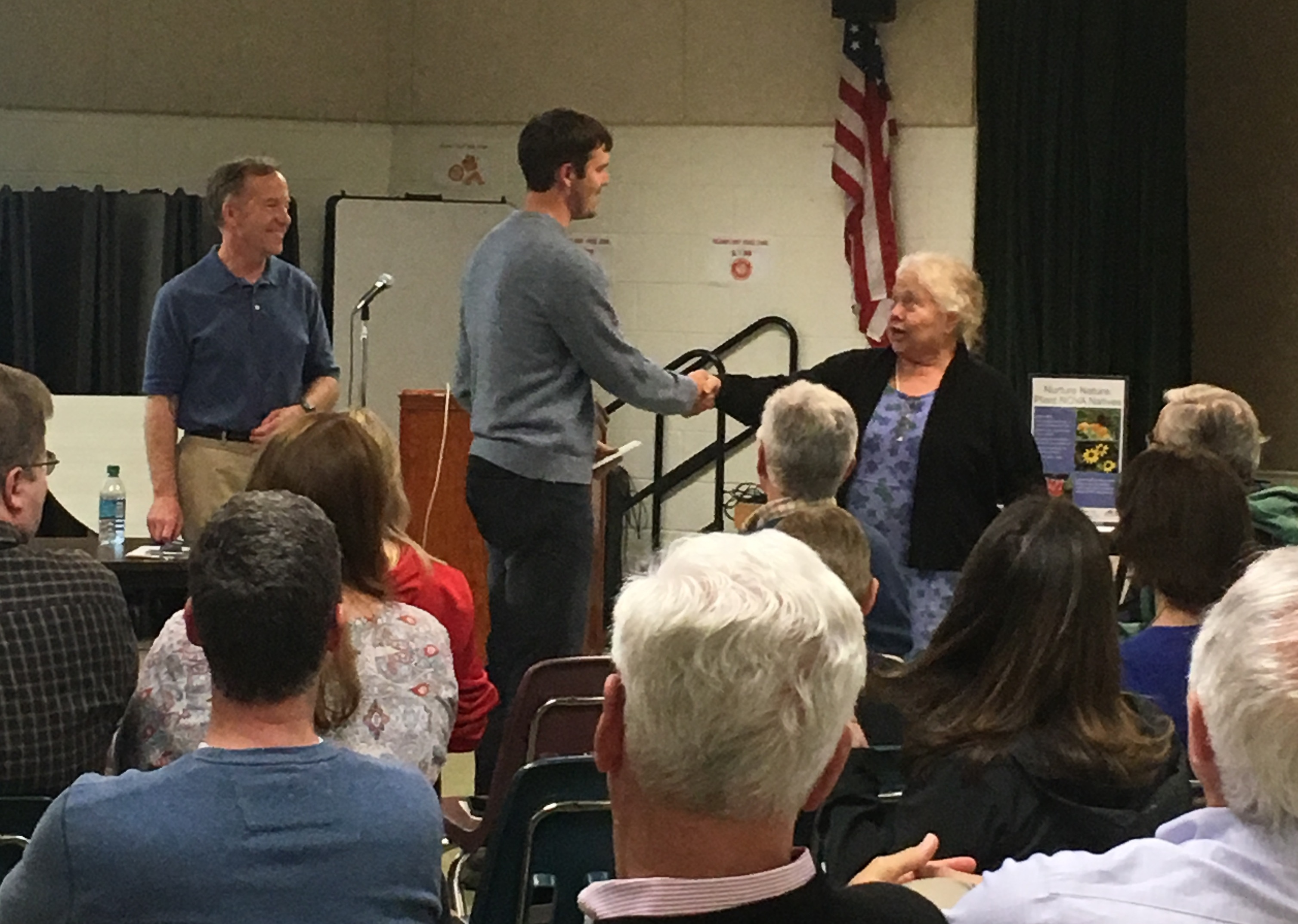 McLean Hamlet garden club President Patricia Frye presents a prize to resident Clay Winters for yard