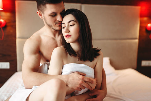 couple-hugging-on-big-white-bed-after-in