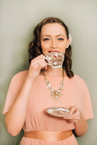 A Girl wearing a pink dress holding a saucer in her left hand and a tea cup up to her mouth.