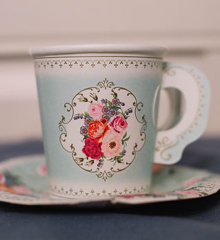A blue floral paper tea cup with matching paper saucer.