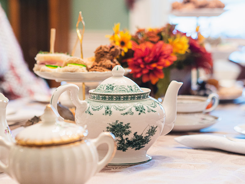 A green and white tea pot with a 3-tiered stand and flowers behind it.