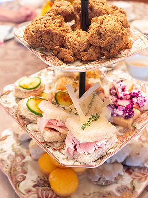 A 3-tiered stand with desserts on bottom, sandwiches in the middle and scones on top
