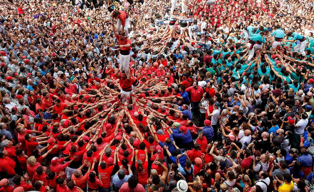 """Thousands of humans, known as the """"Castellers de Barcelona,"""" intricately balance on top of one another to form a human tower"""