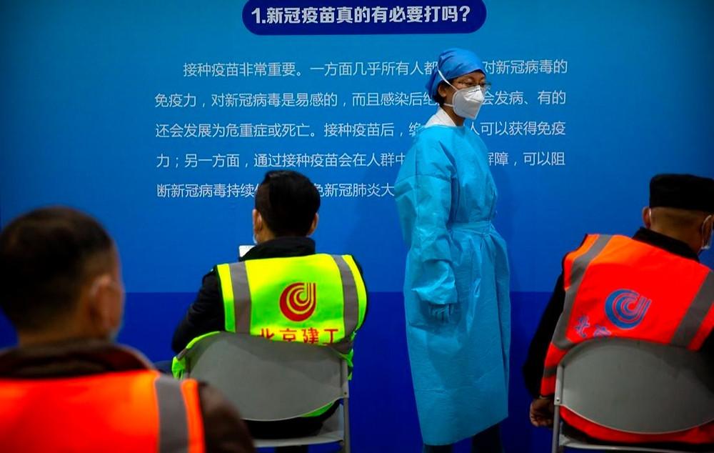 Un trabajador médico que usa equipo de protección monitorea a los pacientes después de que recibieron la vacuna contra el coronavirus en una instalación de vacunación en Beijing, el viernes 15 de enero de 2021.