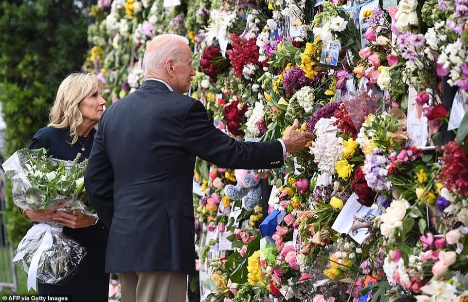 El presidente Biden toca las flores en el muro conmemorativo mientras Jill Biden, la primera dama, observa.