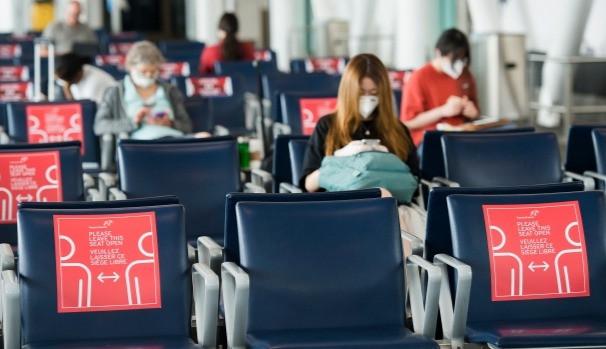 Las personas que usan máscaras obligatorias esperan en su puerta usando distanciamiento físico en el Aeropuerto Internacional Pearson de Toronto.