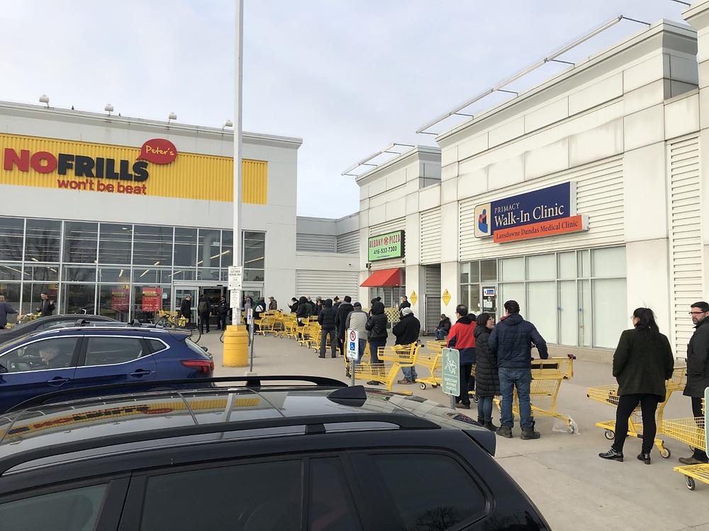 Los compradores hacen fila frente a No Frills en Lansdowne Avenue y Dundas Street.