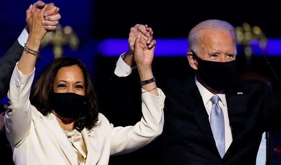 La vicepresidenta electa Kamala Harris se toma de la mano del presidente electo Joe Biden y su esposo Doug Emhoff mientras celebran en Wilmington, Delaware, el 7 de noviembre de 2020.