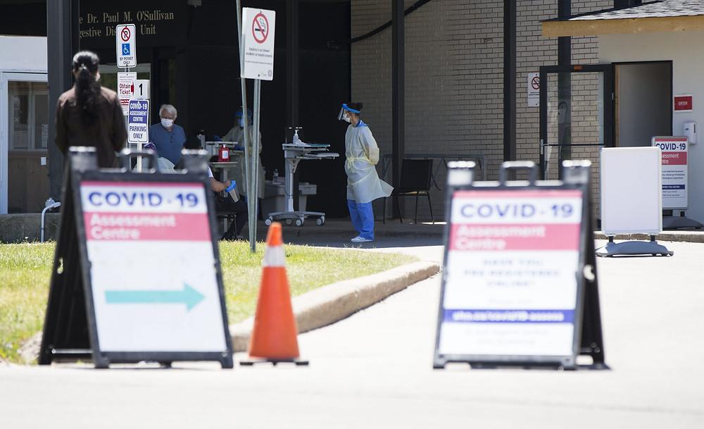 personas que usan máscaras faciales se registran antes de la prueba en un centro de evaluación de COVID-19 de un hospital en Toronto