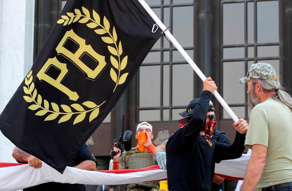 En esta foto del 7 de septiembre de 2020, un manifestante lleva una pancarta de Proud Boys, símbolo de un grupo de derecha, mientras otros miembros comienzan a desplegar una gran bandera estadounidense frente al Capitolio del Estado de Oregón en Salem, Oregón.